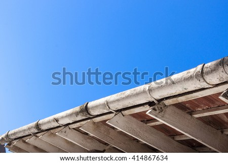 Underview of dirty unkempt gutter and roof trusses against blue sky  - stock photo