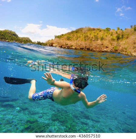Underwater and surface split view in the tropics paradise with snorkeling boy fish and coral reef, above waterline, beautiful view on tropical island. Nusa Penida bali, Indonesia. Holiday concept