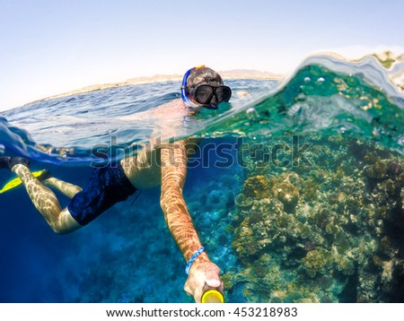 Underwater and surface split view in the tropics paradise with snorkeling man, fish and coral reef, under and above waterline, beautiful view on tropical sea.