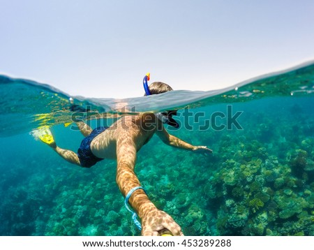 Underwater and surface split view in the tropics paradise with snorkeling man, fish and coral reef, under and above waterline, beautiful view on tropical sea. Egypt. snorkeling vacation concept