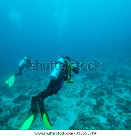 Underwater Background with Silhouettes of Diver in Ocean Blue - stock photo