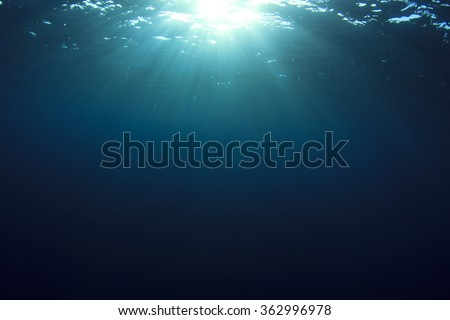 Underwater blue ocean background and sun - stock photo
