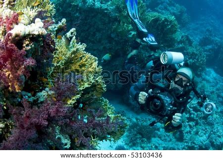 underwater cameraman with DSLR - stock photo