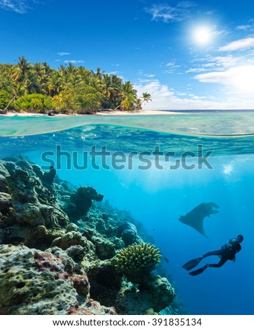 Underwater coral reef with scuba diver and manta - stock photo