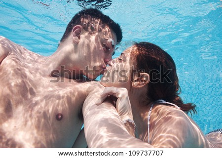 Underwater couple kissing in swimming pool.