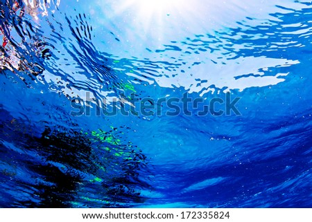 Underwater design pattern. Sun shining trough water sea surface with air bubbles - stock photo