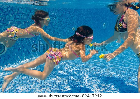 Underwater family in swimming pool. Mother teaching her kids - stock photo