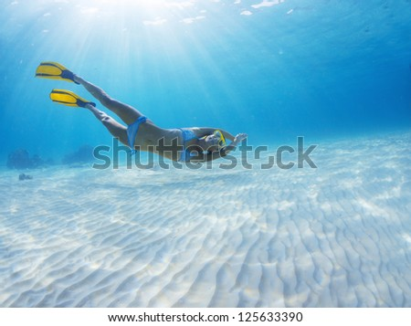 Underwater full length portrait of a woman having fun in a tropical sea over sandy bottom - stock photo