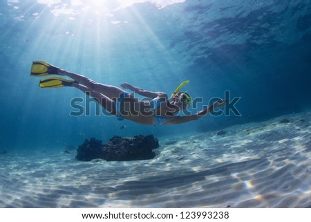Underwater full length portrait of a woman snorkeling in tropical sea over sandy bottom - stock photo