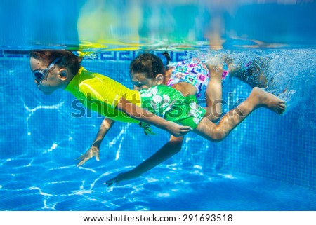 Underwater happy cute girl and boy in swimming pool