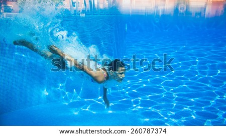 Underwater happy cute girl in swimming pool - stock photo