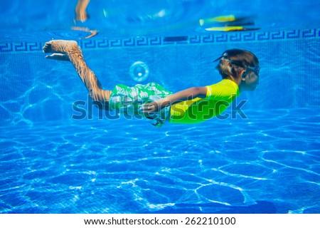 Underwater happy little boy in swimming pool - stock photo