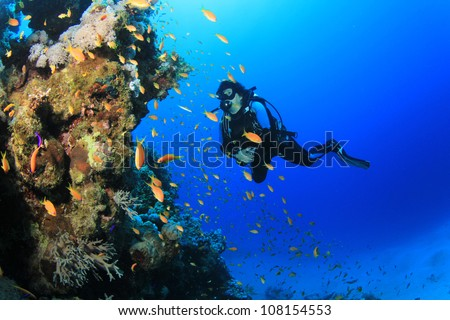 Underwater image of female Scuba Diver with tropical fish on a coral reef