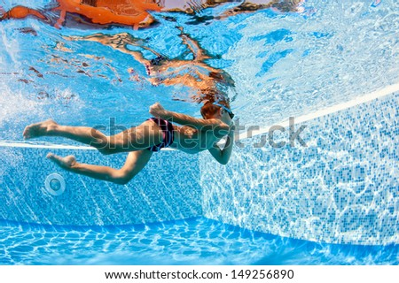 Underwater kid in swimming pool. - stock photo
