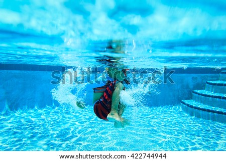 Underwater little boy with mask in swimming pool - stock photo