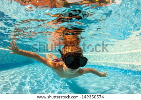 Underwater little kid in swimming pool with black mask.