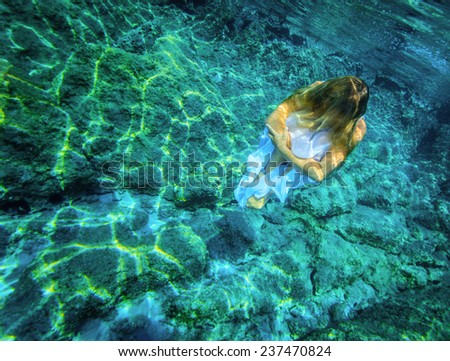 Underwater meditating, beautiful woman sitting on the bottom of the sea, zen balance, active lifestyle, summer time relaxation concept