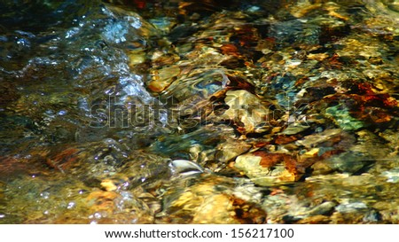 Underwater Multicolored rock and pebbles in clear pond - stock photo