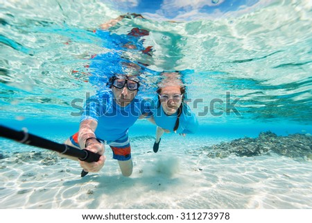 Underwater photo of a couple snorkeling in ocean and making selfie with stick - stock photo