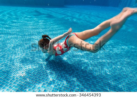 Underwater photo of adorable little girl diving and swimming in pool on summer vacation