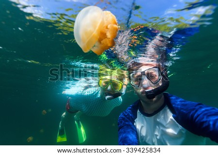 Underwater photo of couple snorkeling with endemic golden jellyfish in lake at Palau. Snorkeling in Jellyfish Lake is a popular activity for tourists to Palau. - stock photo