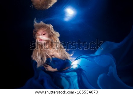 underwater photo pretty young girl  with blond long hair wearing blue fabric - stock photo