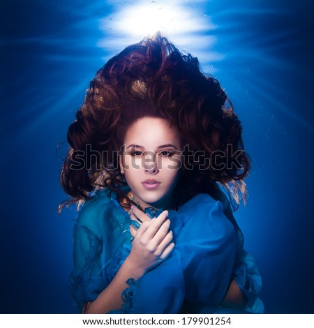 underwater photo pretty young girl with dark long hair wearing blue fabric - stock photo