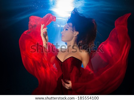 underwater photo pretty young girl  with dark long hair wearing red dress - stock photo