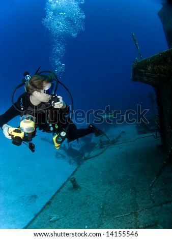 Underwater Photographer looking at a Sunken Ship with Regulator in her hand.