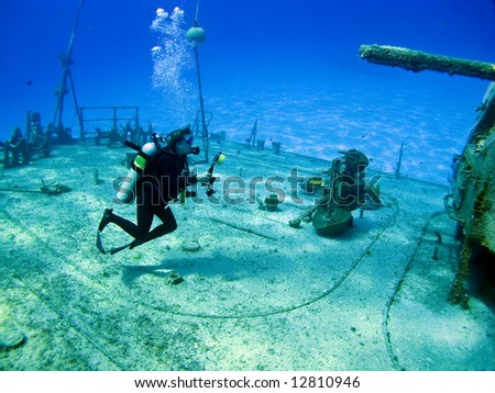 Underwater Photographer shooting the shipwreck Tibbits in Cayman Brac - stock photo