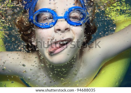 Underwater picture of a young boy swimming and playing - stock photo