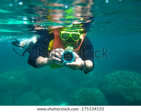 Underwater portrait of a man snorkeling in Andaman Sea with his camera.