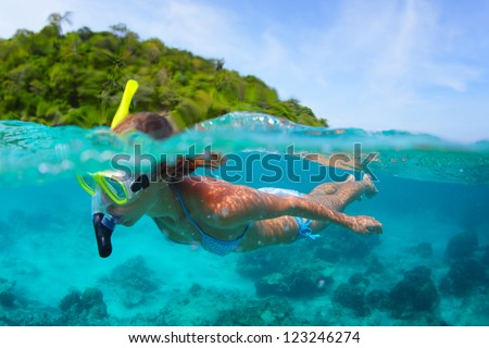 Underwater portrait of a woman snorkeling in tropical sea. - stock photo