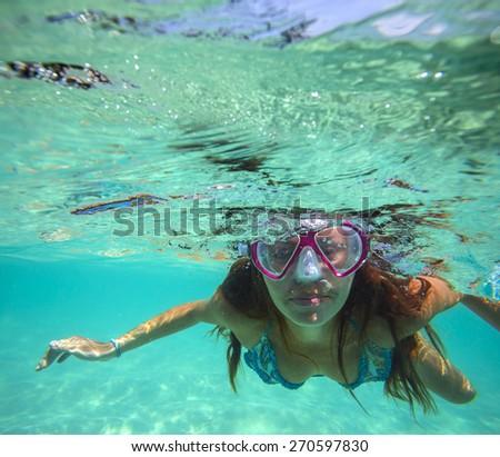 Underwater Portrait of a Yong Woman Snorkeling in Ocean. - stock photo