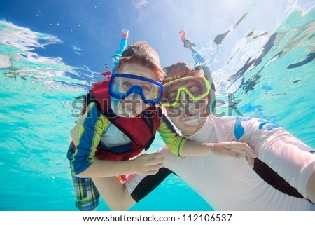 Underwater portrait of father and son snorkeling together