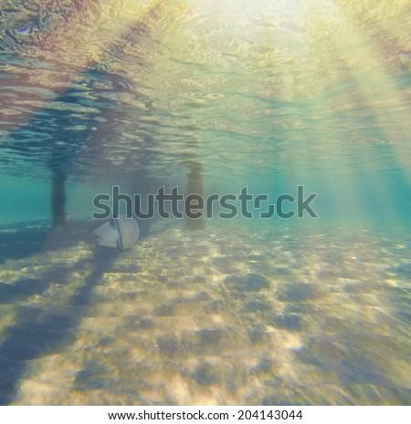 Underwater ripples of sunlight reflected on a sandy sea floor  - stock photo