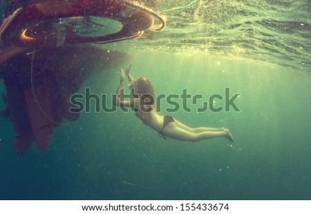 Underwater shoot from a bottom of a young woman