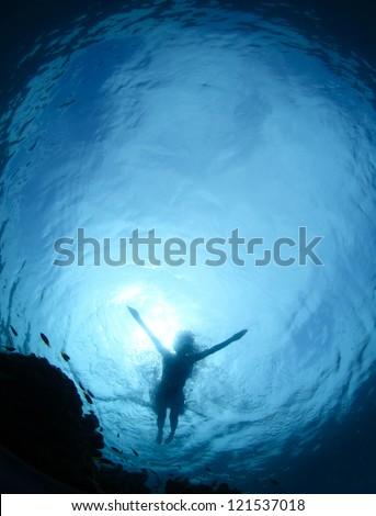 Underwater shoot from a bottom of a young woman snorkeling on a sea surface - stock photo