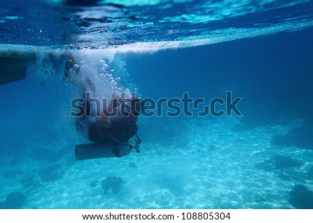 Underwater shoot of a diver doing back flip from a boat