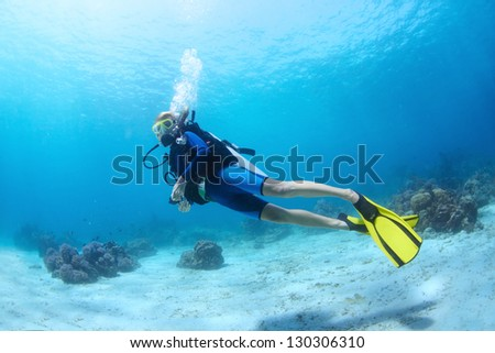 Underwater shoot of a diver swimming in a blue clear water near a bottom - stock photo