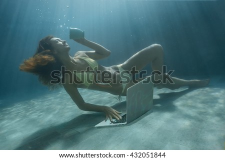Underwater shoot of a relaxed daydreaming beauty looking at laptop computer screen, holding coffee mug, smiling woman