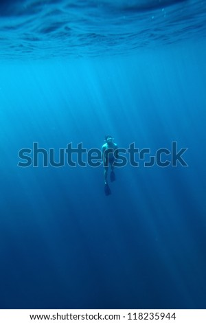 Underwater shoot of a young athlete fining from a depth to surface on a breath hold - stock photo