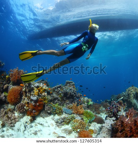 Underwater shoot of a young lady snorkeling and diving on a breath hold over vivid coral reef of tropical island with boat silhouette on surface - stock photo