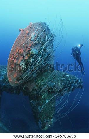 Underwater shoot of female scuba diver swimming near propeller of sunken battleship - stock photo