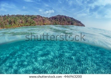 Underwater shot of a sandy sea bottom and green tropical island with cloudy sky above sea surface - stock photo