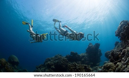 Underwater shot of the couple gliding in depth of tropical sea at sunny day
