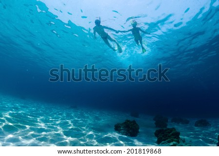 Underwater shot of the couple snorkeling on sea surface - stock photo