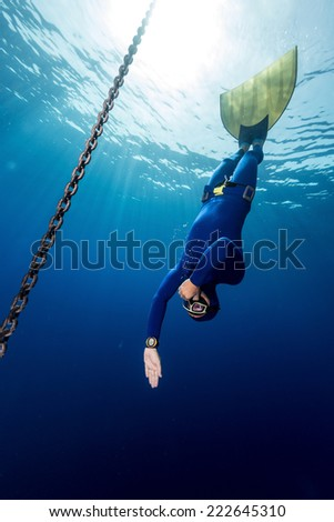 Underwater shot of the free diver in monofin descending along the metal chain. Constant weight discipline