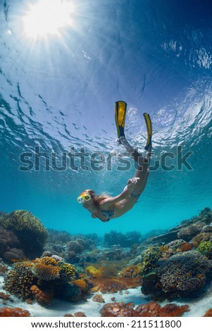 Underwater shot of the young lady gliding over vivid coral reef on a breath hold - stock photo