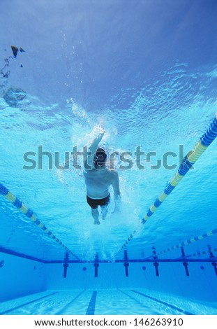 Underwater shot of young male athlete doing backstroke in swimming pool - stock photo